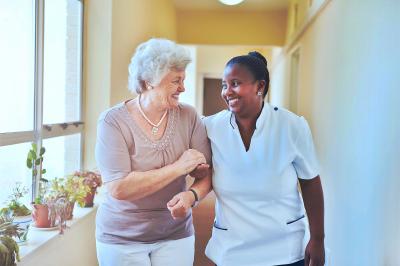 smiling home caregiver and senior woman