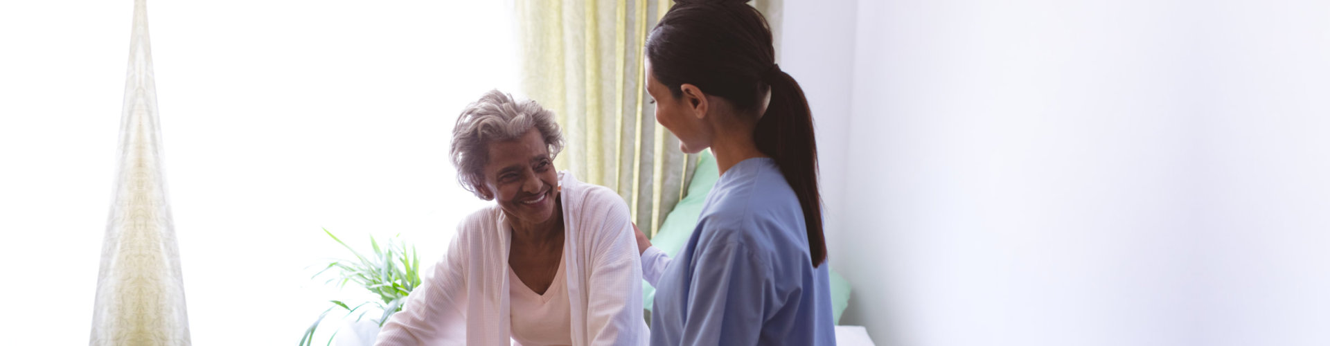young caregiver assisting senior woman to walk