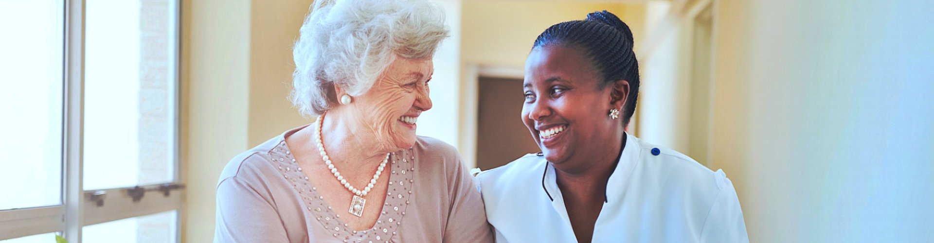 smiling home caregiver and senior woman
